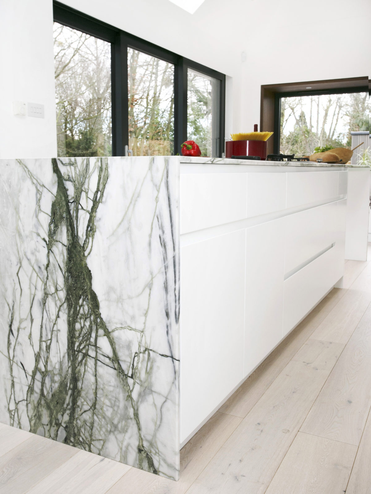 White lacquered island with calacatta verde marble worktop