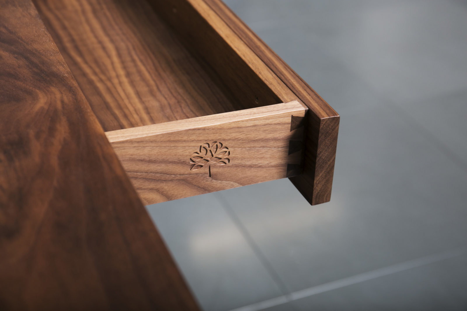 Solid walnut drawer with dovetail detail and engraved motif