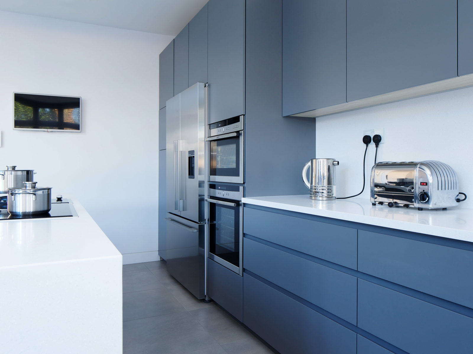 Grey matt lacquered kitchen with long handless drawers