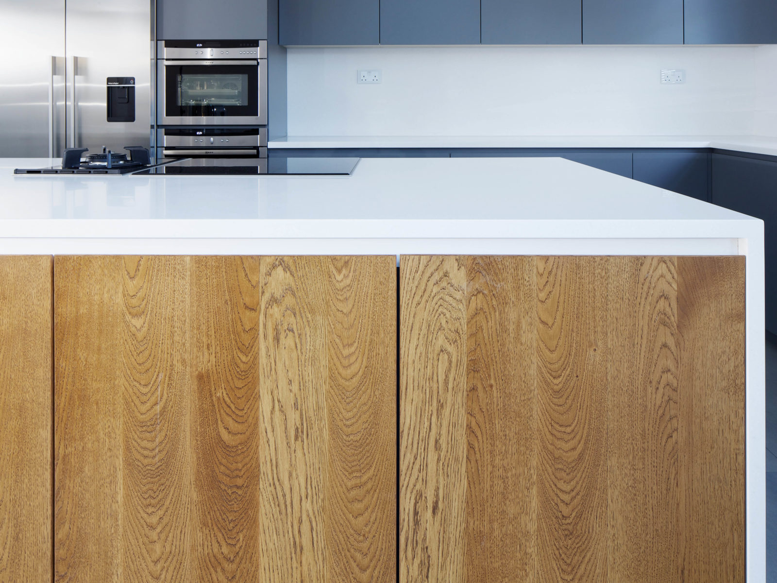 Handless kitchen island with solid oak doors and Antartica Corian worktop