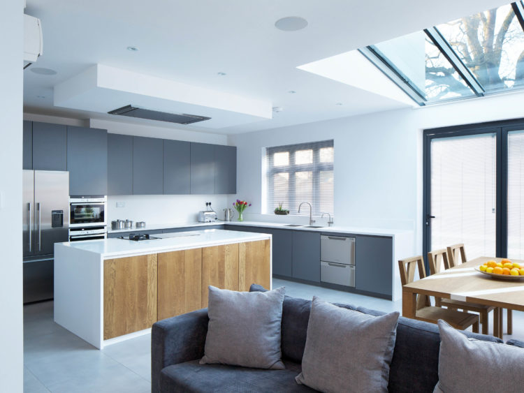 Open plan kitchen with matt grey lacquered doors, Antartica Corian worktop and splashback, solid oak island doors