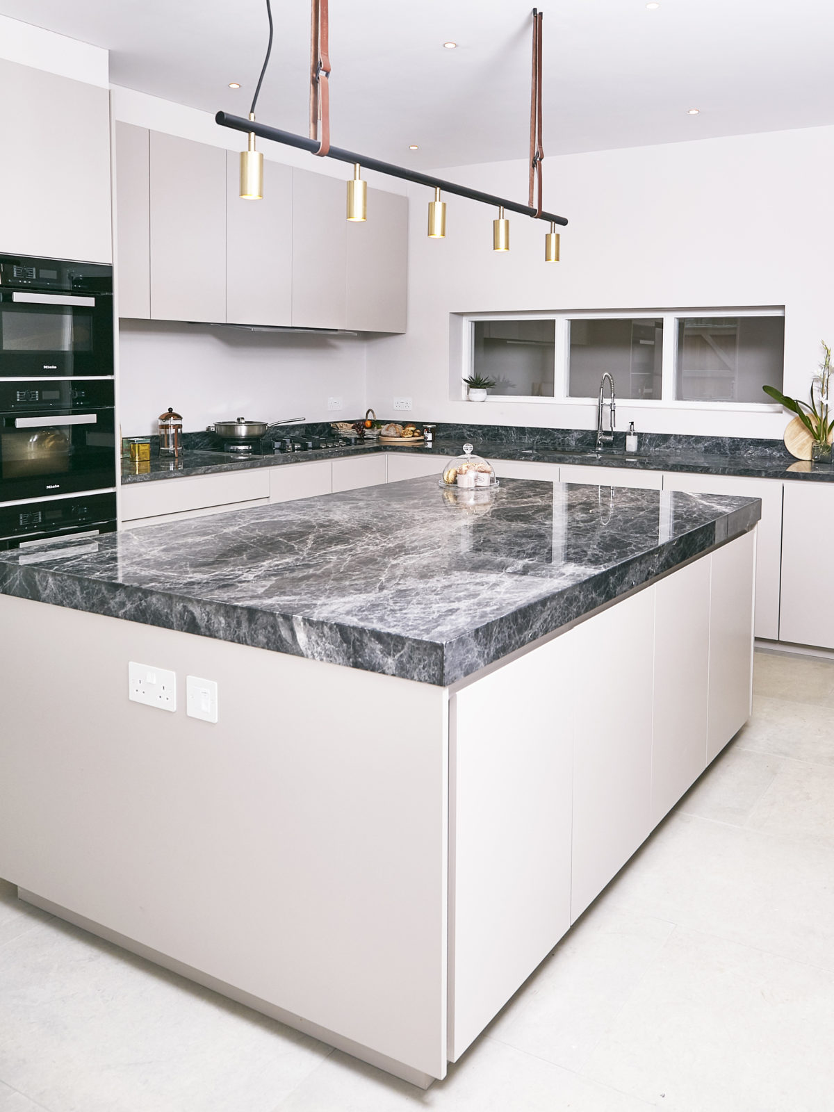Matt lacquered kitchen island with thick Savana grey marble worktop