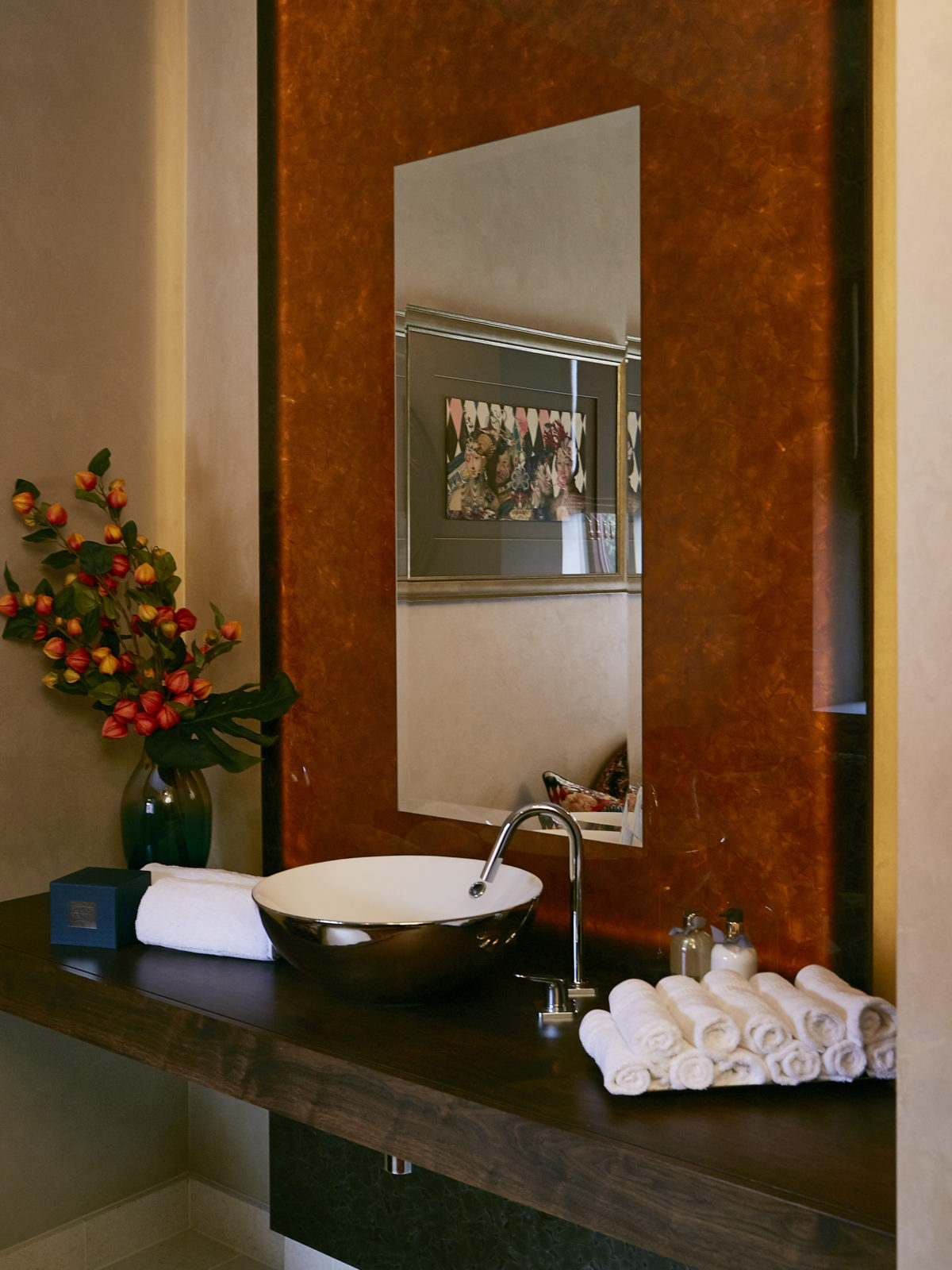 Walnut bathroom worktop with backlit recycled glass mirror wall