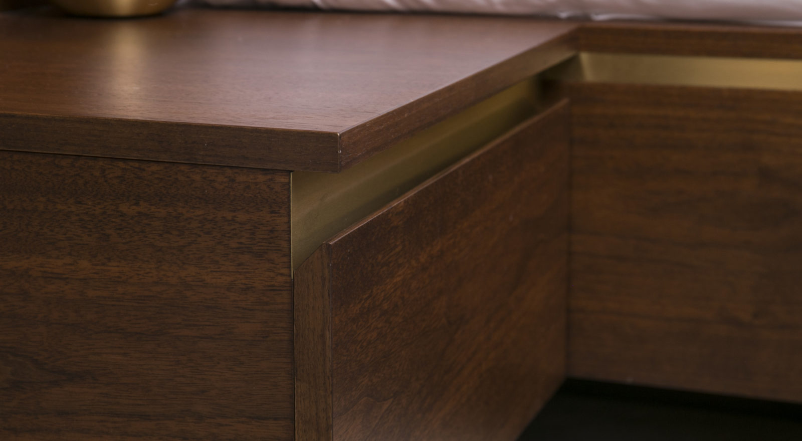 handless walnut bedside table with satin brass detail