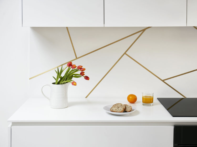 Satin brass inlay splashback design in a white kitchen with Corian worktop