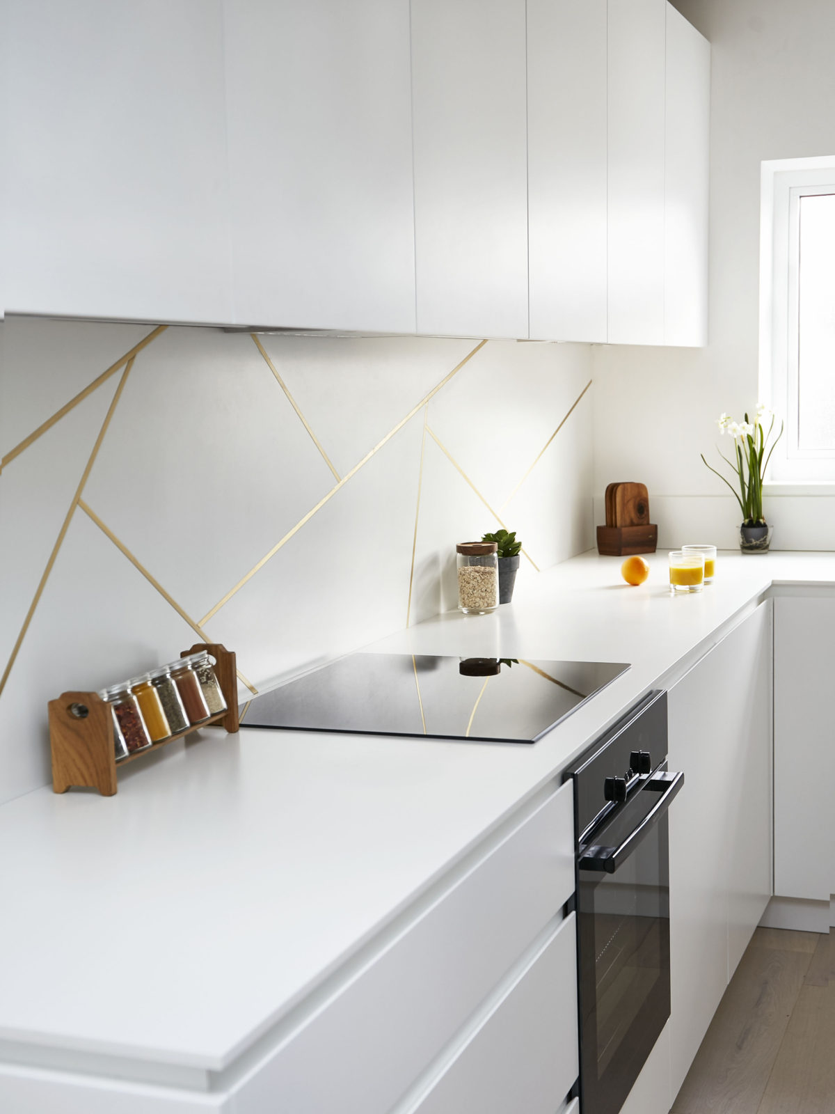 White lacquered handless kitchen with white Corian worktop and satin brass inlay splashback design