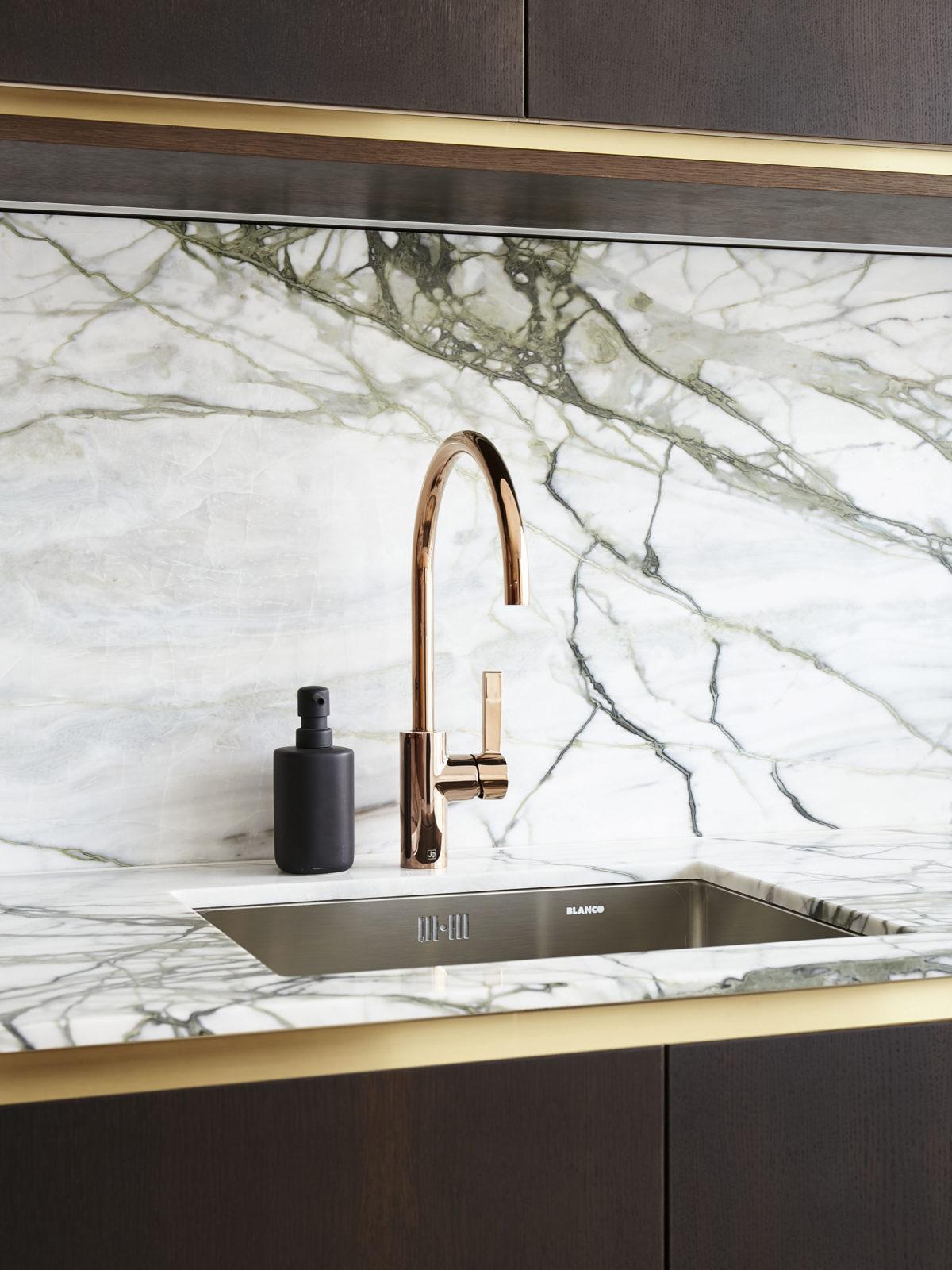 Calacatta marble worktop and splachback, dark wood kitchen cabinets and brass detailing