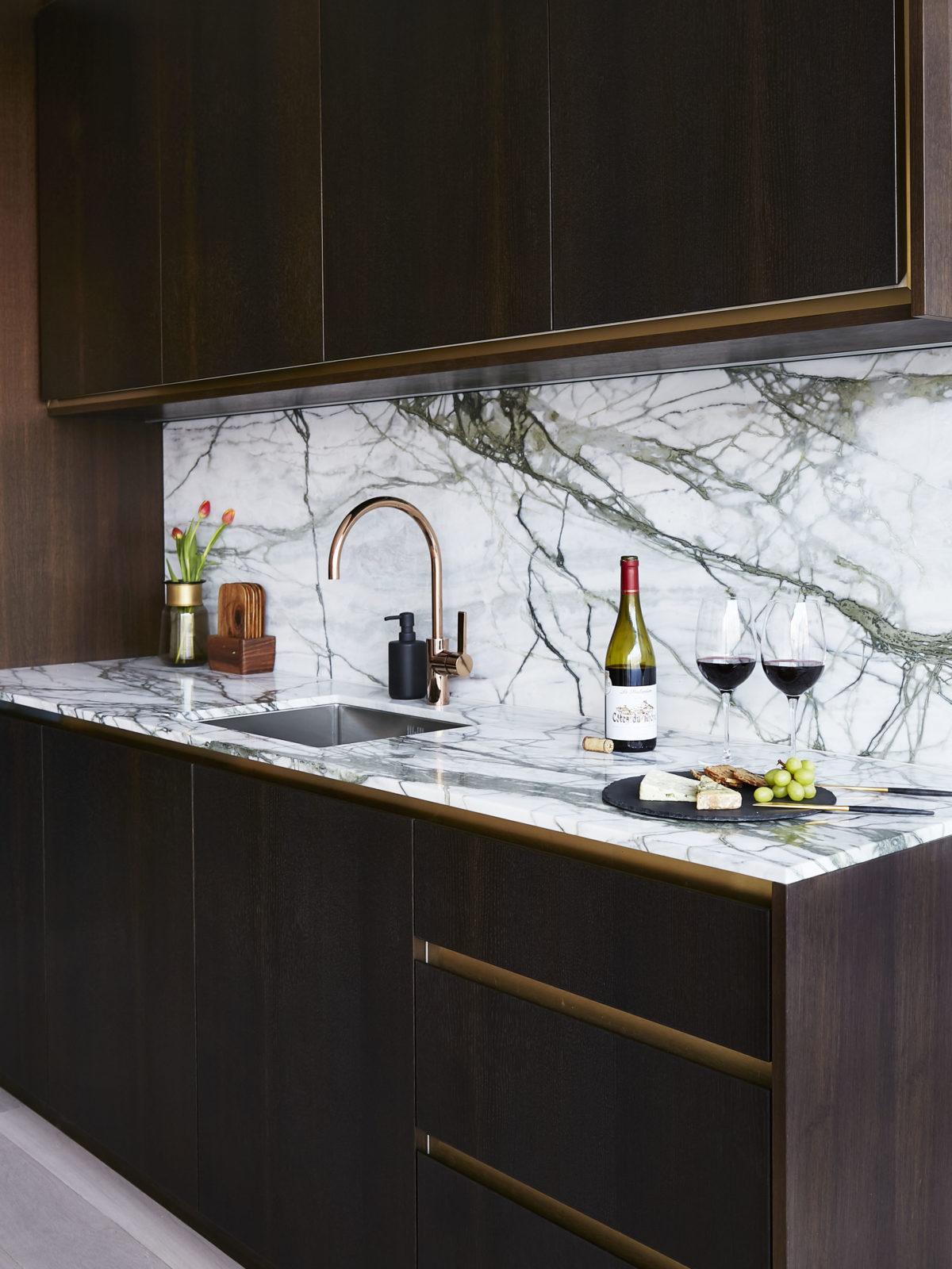 handleless fumed oak kitchen with satin brass strips