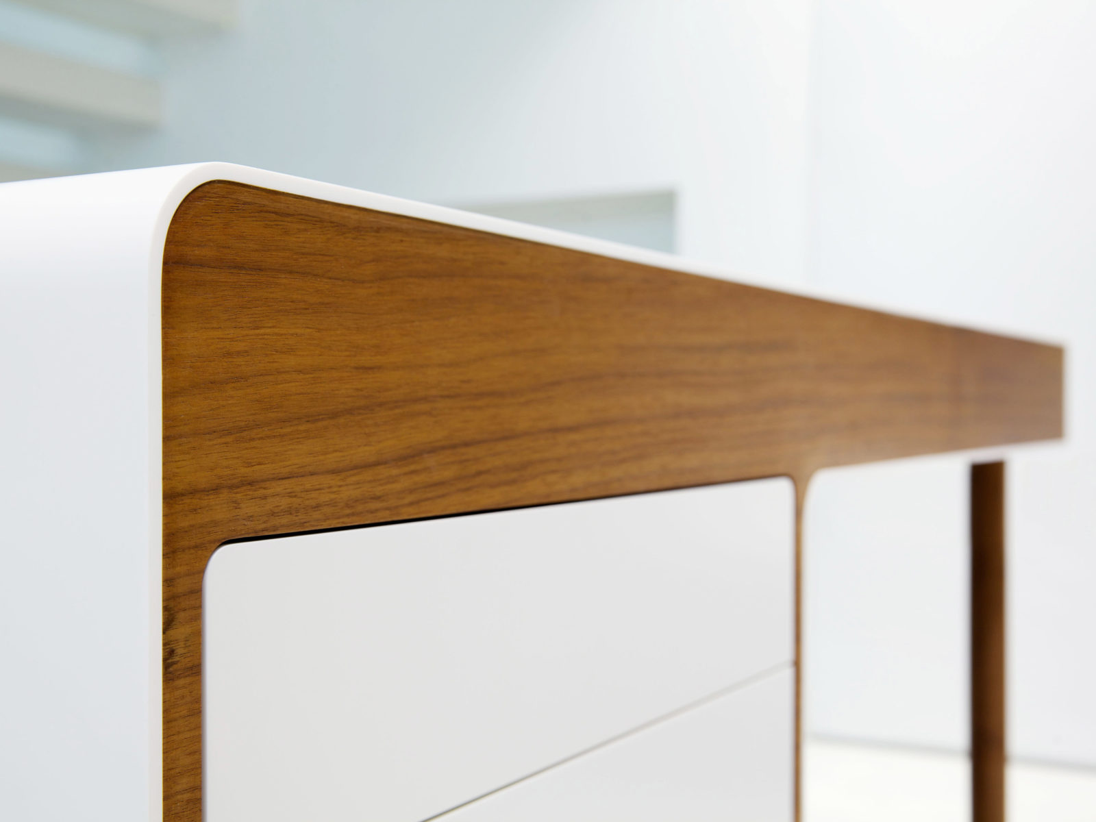 curved Corian desk with walnut venner details