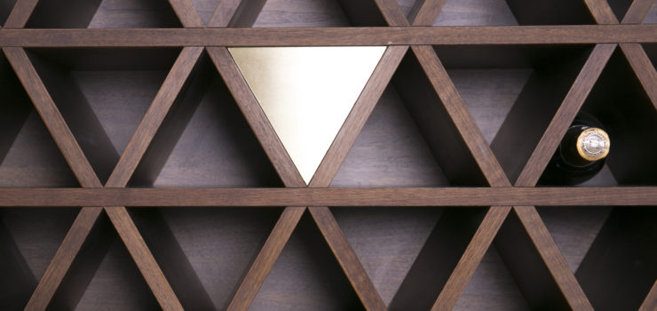 Solid walnut wine cellar wall with brass inserts